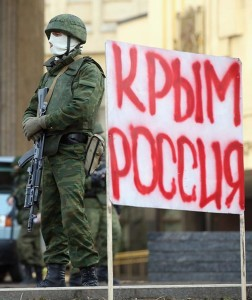 """SIMFEROPOL, UKRAINE - MARCH 01:  Heavily-armed soldiers without identifying insignia guard the Crimean parliament building next to a sign that reads: """"Crimea Russia"""" after taking up positions there earlier in the day on March 1, 2014 in Simferopol, Ukraine. The soldiers' arrival comes the day after soldiers in similar uniforms stationed themselves at Simferopol International Airport and Russian soldiers occupied the airport at nearby Sevastapol in moves that are raising tensions between Russia and the new Kiev government. Crimea has a majority Russian population and armed, pro-Russian groups have occupied government buildings in Simferopol.  (Photo by Sean Gallup/Getty Images)"""