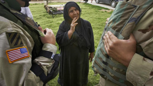 An elderly woman pleads with US Army Captain Roy Bolar, left, of Aberdeen, Ohio through an Iraqi translator, right, whose name is not given for fear of retribution, for the release of her son, who is being held by US forces, in the outskirts of Baquoba 57 kilometers (35 miles) north of Baghdad, Iraq, Monday, May 2, 2005. Soldiers from the Third Infantry Division, Third Brigade, 2-62 Armor Battalion found an AK-47 based on intelligence from an Iraqi man detained earlier on charges of setting a roadside bomb. (AP Photo/Jacob Silberberg)