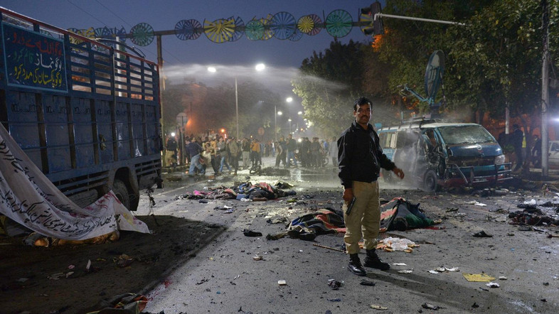 A Pakistani police officer stands alert beside the bodies of victims at the site after a powerful explosion in Lahore on February 13, 2017. At least 10 people were killed and 71 injured when an apparent Taliban suicide blast ripped through a protest in Pakistan's Lahore on February 13, officials said, shattering the city's growing sense of security. / AFP PHOTO / STR