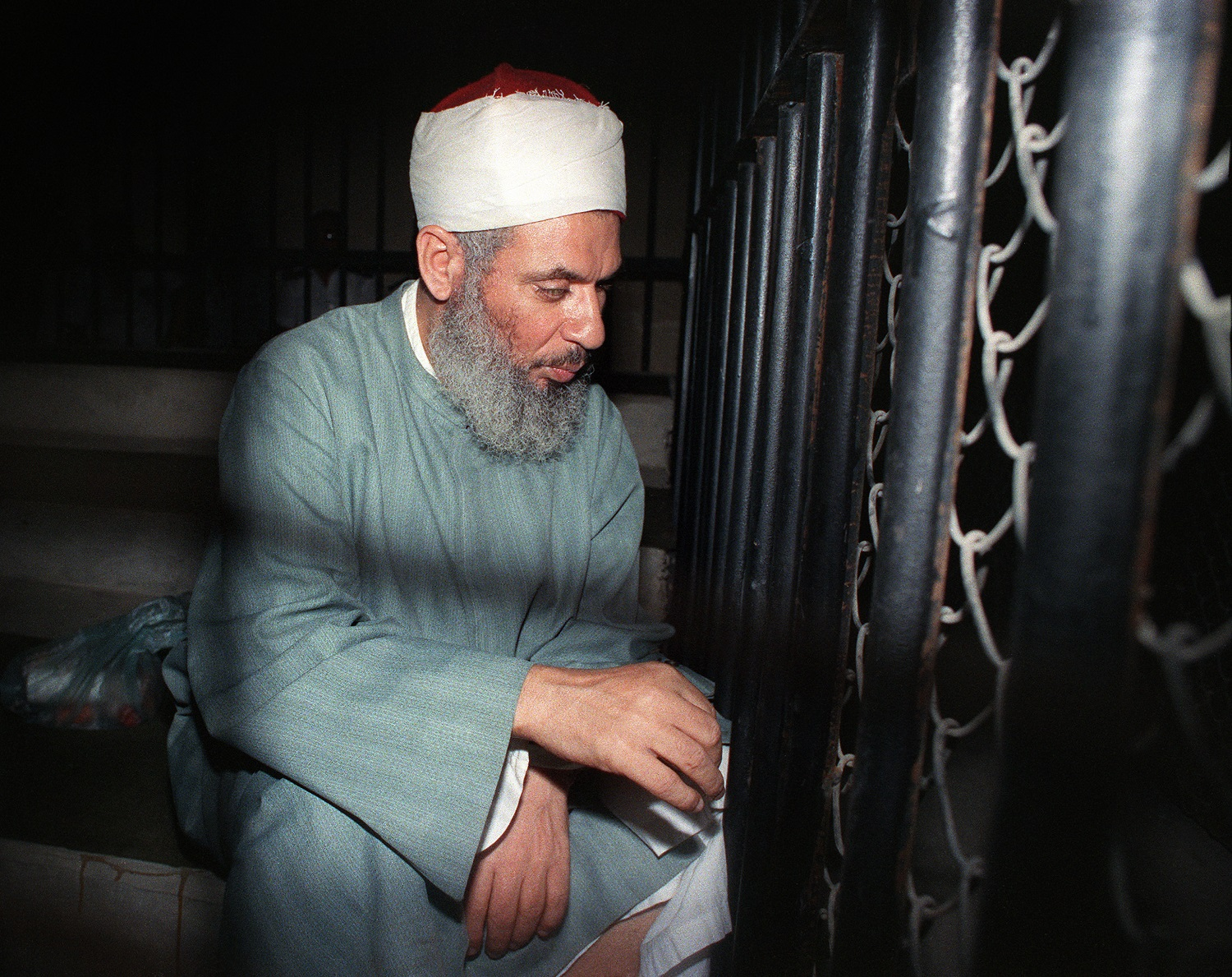 Blind Sheikh Omar Abdel Rahman sits and prays inside an iron cage at the opening of court session, 06 August 1989 in Cairo. Abdel-Rahman, spiritual leader of Egypt's main armed group the Moslem fundamentalist Jamaa Islamiyya, was jailed for life in January 1996 for his role in terrorist attacks, including blowing up the World Trade Center in New York in February 1993 and an assassination bid against Egyptian President Mubarak. / AFP PHOTO / MIKE NELSON
