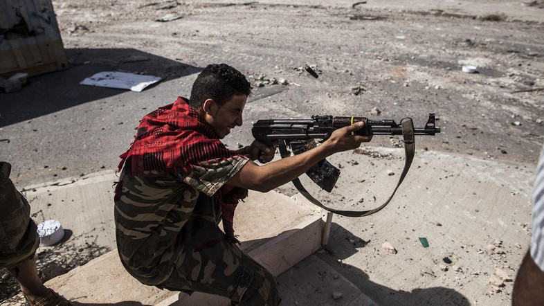 A fighter of the Libyan forces, affiliated to the Tripoli government, shoots against Islamic State positions, in Sirte, Libya, Thursday, Sept. 22, 2016. The new offensive to retake the last district under control of Islamic State militants has left over over 5 Libyan fighters dead and wounded around 70. (AP Photo/Manu Brabo)