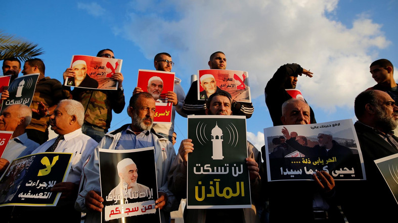 Supporters of Sheikh Raed Salah, head of Islamic Movement's northern branch, protest in the Israeli-Arab town of Umm el-Fahm against the initial approval of a bill to enforce lowering the volume of mosque loudspeakers calling worshippers to prayer, November 17, 2016. The placards reads