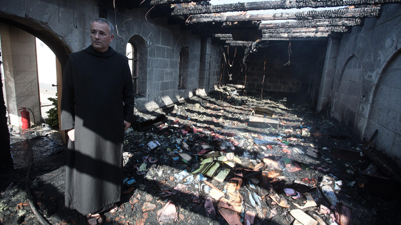 A priest inspects the damage at a room located on the complex of the Church of the Multiplication at Tabgha, on the shores on the Sea of Galilee in northern Israel, on June 18, 2015, in the aftermath of a suspected arson attack. The suspected attack totally destroyed an external atrium of the Christian shrine, which is believed by many Christians to be the place where Jesus fed the 5,000 in the miracle of the five loaves and two fish, with a church adviser pointing the finger at Jewish extremists. AFP PHOTO / MENAHEM KAHANA / AFP PHOTO / MENAHEM KAHANA