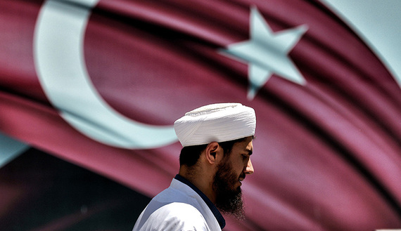 An imam passes the Turkish flag during a demonstration in support of Turkey's President Erdogan (not pictured) at the Sarachane park in Istanbul on July 19, 2016.  Turkey has demanded the resignation of 1,577 university deans suspected of being connected with Friday's attempted coup, state-run news agency Anadolu reported July 19. The country's higher education board made the demand for deans at state and private foundation universities to resign, Anadolu said.  / AFP / ARIS MESSINIS        (Photo credit should read ARIS MESSINIS/AFP/Getty Images)