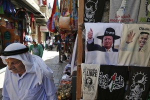 A Palestinian walks past a souvenir shop displaying T-shirts bearing images of US President Barack Obama (R) wearing a kaffiyeh and president-elect Donald Trump (L) dressed as a Hasidic Jew for sale in a souvenir shop in Jerusalem's Old City November 10, 2016. Donald Trump's shock election as president will likely result in a US tilt towards Israel that puts a Palestinian state even further out of reach, his own campaign team and analysts say. / AFP / AHMAD GHARABLI        (Photo credit should read AHMAD GHARABLI/AFP/Getty Images)