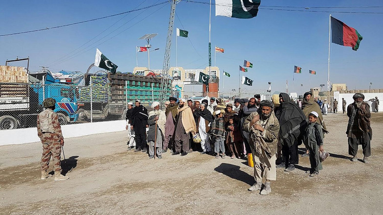 In this photograph taken on January 7, 2017, travellers are watched by Pakistan security personnel as they wait to cross the border between Pakistan and Afghanistan at Chaman.  For decades Afghan and Pakistani merchants crossed freely at Chaman, a dusty, wind-swept frontier town in Pakistan's southwest, but an unprecedented bid by Islamabad to impose border controls is sparking fears for bilateral trade.  Chaman is one of just two major crossings from Afghanistan into Pakistan, where until recently border controls were virtually absent along the disputed colonial-era line crossed with impunity by traders and travellers. / AFP PHOTO / Issam AHMED