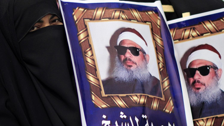 "Egyptian protesters hold posters showing Sheikh Omar Abdel-Rahman, who is imprisoned in the US, and call for his release outside a court in Cairo, Egypt, Sunday, Feb. 26, 2012. Egypt went forward with a trial Sunday that has plunged relations with the U.S. into the deepest crisis in decades, prosecuting 16 Americans and 27 other employees of pro-democracy groups on charges they used foreign funds to foment unrest. The Arabic writing on the banners reads:""Freedom for Sheikh Omar Abdel Rahman"". (AP Photo/Khalil Hamra)"