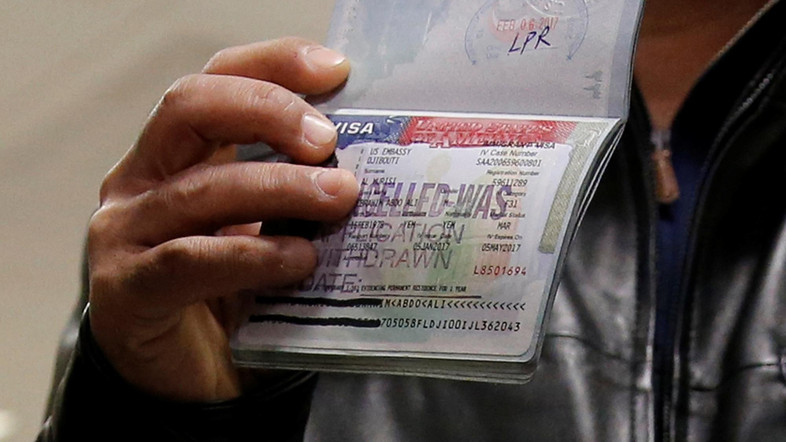 A member of the Al Murisi family, Yemeni nationals who were denied entry into the U.S. last week because of the recent travel ban, shows the cancelled visa in their passport from their failed entry to reporters as they successfully arrive to be reunited with their family at Washington Dulles International Airport in Chantilly, Virginia, U.S. February 6, 2017.  REUTERS/Jonathan Ernst - RTX2ZVTY
