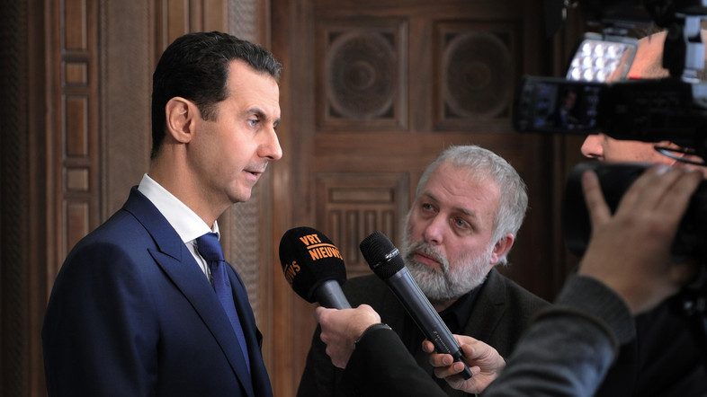 A handout picture released by the official Syrian Arab News Agency (SANA) on February 7, 2017 shows Syrian President Bashar al-Assad (L) giving an interview to a Belgian media outlet.    / AFP PHOTO / SANA / -