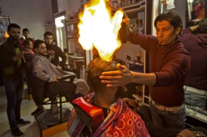 Ramadan Edwan, a Palestinian barber, uses fire in a hair-straightening technique with a client at his salon in the Rafah refugee camp, in the southern Gaza Strip on February 1, 2017. / AFP PHOTO / MAHMUD HAMS