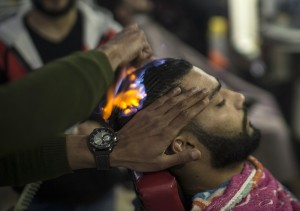 A client sits in a hair salon as barber Ramadan Edwan performs a technique that utilises fire to straighten his hair, in the Rafah refugee camp, in the southern Gaza Strip on February 1, 2017. / AFP PHOTO / MAHMUD HAMS