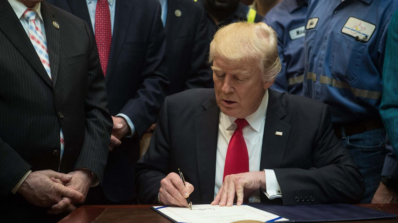 US President Donald Trump signs a bill eliminating regulations on the mining industry in the Roosevelt Room at the White House in Washington, DC, on February 16, 2017. The new law nullifyies a rule from the USDepartment of the Interior aimed at protecting streams. / AFP PHOTO / NICHOLAS KAMM