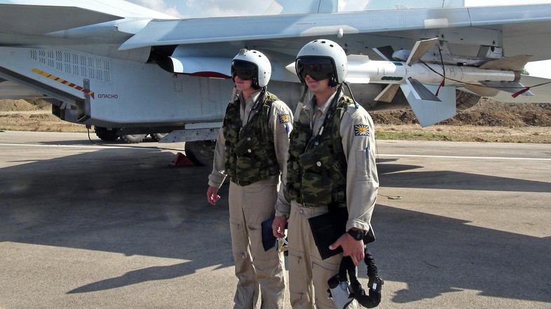 In this photo taken on Monday, Oct. 5, 2015, Russian pilots stand outside their Su-30 jet fighter, armed with air-to-air missiles, before a take off at Hmeimim airbase in Syria. NATO also strongly criticized the Russian air campaign in Syria that began Wednesday. (AP Photo/Dmitry Steshin, Komsomolskaya Pravda, Photo via AP)