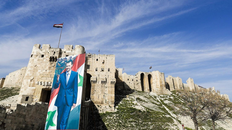 A picture taken on March 9, 2017 in the northern Syrian city of Aleppo which was recaptured by government forces in December 2016, shows giant banners of President Bashar al-Assad outside the historic citadel on the outskirts of the old city. / AFP PHOTO / JOSEPH EID