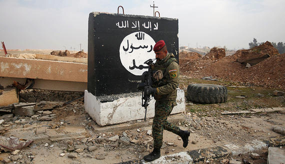 An Iraqi soldier walks next to a wall painted with the black flag commonly used by Islamic State militants, during a battle with Islamic State militants near Arabi neighborhood, north of Mosul, Iraq, January 21, 2017. REUTERS/Khalid al Mousily - RTSWOU6