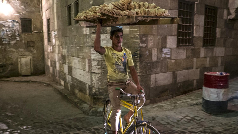 An Egyptian bread seller rides his bicycle as Muslim worshipers break the day-long fast during the holy month of Ramadan in Cairo Khan el-Khalili district on July 8, 2014. During the holy month of Ramadan, Muslims are supposed to go without food, drink, smoking and sex and to refrain from impure thoughts from sunrise to sunset. AFP PHOTO / KHALED DESOUKI / AFP PHOTO / KHALED DESOUKI