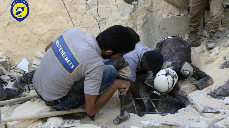 In this picture taken, Tuesday, Oct. 11, 2016, provided by the Syrian Civil Defense group known as the White Helmets, Syrian Civil Defense workers search underground in rebel-held eastern Aleppo, Syria. Activists and rescue workers say an intensive day of bombing on besieged rebel-held parts of Aleppo has left at least 25 people dead, including five children. Rescue workers pulled at least one boy alive from under the rubble late Tuesday night. The Britain-based Syrian Observatory for Human Rights says Wednesday that Tuesday's bombings killed 25 people. The Syrian Civil Defense, a team of first responders, and activist media platform Aleppo Media Center put the death toll at 41. (Syrian Civil Defense- White Helmets via AP)