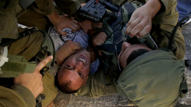 Israeli soldiers restrain a Palestinian man as troops try to arrest him in the flashpoint city of Hebron, in the Israeli-occupied West Bank, on September 20,2016. The man was named by family members, who witnessed his arrest, as Mohammed al-Kawasmi, 30, whom they said suffers from psychological troubles. Earlier in the day, a Palestinian teenager tried to stab an Israeli soldier near Hebron before being shot dead, officials said, the latest death in a flare-up of violence.  / AFP PHOTO / HAZEM BADER