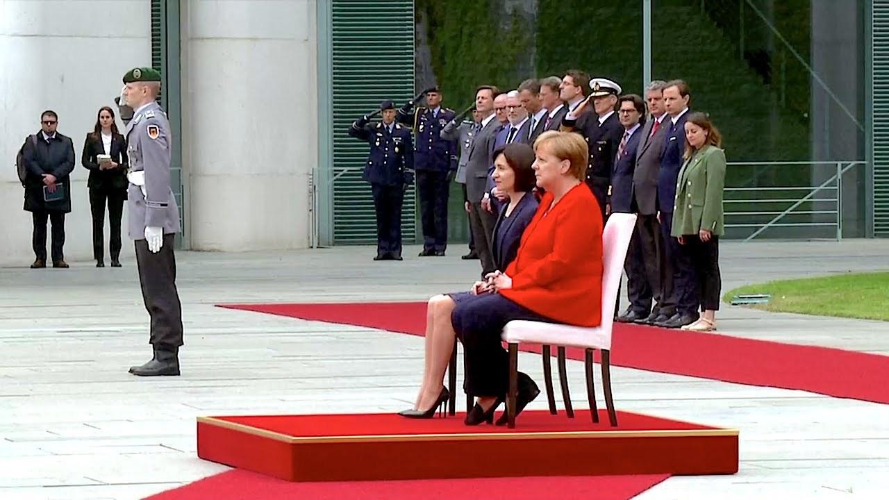 Angela Merkel himni yenə oturaraq dinləyib